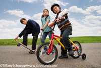 Children stock photo of young kids with skateboards, bikes, and scooters. The children are a mixed ethnic group.